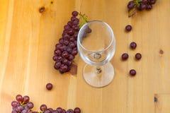 Vidro de vinho tinto com as uvas frescas em torno dele em uma tabela de madeira nele e imagens de stock