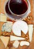 Vidro de vinho tinto e parcela de queijos cortados fotografia de stock