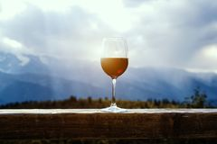 Vidro de vinho tinto em um piquenique que está em uma tabela de madeira na frente do fundo bonito da montanha Imagens de Stock Royalty Free