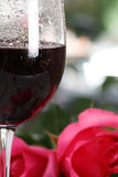 Vidro de vinho vermelho com rosas e gotas da água Imagens de Stock Royalty Free