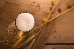 Vidro do arroz da cerveja e da cevada na tabela de madeira na luz dourada T Imagens de Stock Royalty Free