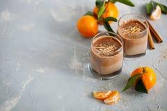 Vidro do cacau quente com entusiasmo alaranjado do leite e da tangerina em um claro - close-up azul do fundo imagens de stock