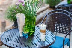 Vidro do café do cappuccino do caramelo na tabela no café imagens de stock royalty free