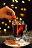 Vidro do close up do vinho ferventado com especiarias com laranja e canela à disposição da mulher no fundo preto escuro foto de stock royalty free