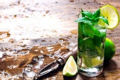 Vidro do cocktail, do gelo, da faca e de fatias frescos de cal em uma tabela de madeira Fotos de Stock