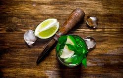 Vidro do cocktail, do gelo, da faca e de fatias frescos de cal em uma tabela de madeira Imagens de Stock