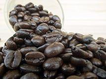 Vidro do excesso dos feijões de café Foto de Stock Royalty Free