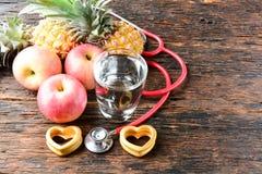 Vidro do fruto, do coração, do estetoscópio e de água para saudável e o corpo s Imagem de Stock Royalty Free
