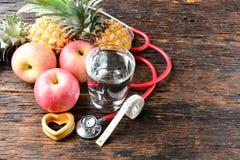 Vidro do fruto, do coração, do estetoscópio e de água para saudável e o corpo s Fotos de Stock Royalty Free