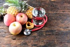 Vidro do fruto, do coração, do estetoscópio e de água para saudável e o corpo s Imagens de Stock Royalty Free