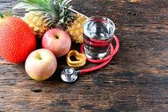 Vidro do fruto, do coração, do estetoscópio e de água para saudável e o corpo s Imagem de Stock