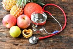 Vidro do fruto, do coração, do estetoscópio e de água para saudável e o corpo s Fotos de Stock