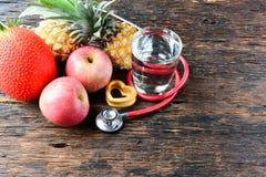 Vidro do fruto, do coração, do estetoscópio e de água para saudável e o corpo s Fotografia de Stock Royalty Free