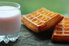 Vidro do iogurte da framboesa e dois waffles recentemente cozidos contra o fundo verde borrado Imagem de Stock Royalty Free