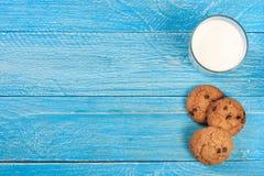 Vidro do leite com cookies de farinha de aveia em um fundo de madeira azul com espaço da cópia para seu texto Vista superior imagem de stock