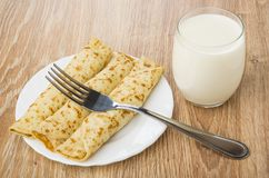 Vidro do leite, da placa das panquecas com enchido e da forquilha fotografia de stock