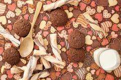 Vidro do leite e das cookies no guardanapo escuro com imagem dos corações imagem de stock