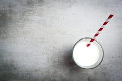 Vidro do leite e de uma palha bebendo vermelha e branca em um t concreto Fotos de Stock Royalty Free