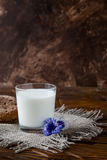 Vidro do leite na tabela de madeira com flores bonitas Imagem de Stock