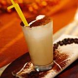 Vidro do macchiato do latte com pó do chockolate e uma palha Imagens de Stock