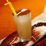 Vidro do macchiato do latte com pó do chockolate e uma palha Imagem de Stock
