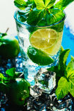 Vidro do mojito com palha vermelha do close-up do cubo de gelo do cal e da hortelã no fundo azul Imagem de Stock Royalty Free
