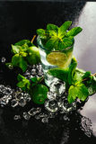 Vidro do mojito com palha vermelha do close-up do cubo de gelo do cal e da hortelã no fundo escuro Fotos de Stock Royalty Free