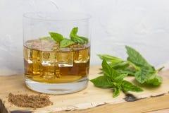 Vidro do rum com gelo e hortelã na madeira Imagem de Stock