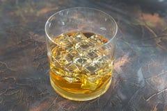Vidro do rum com gelo no fundo preto Fotos de Stock Royalty Free