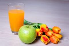 Vidro do suco, da maçã e das tulipas na tabela Fotografia de Stock Royalty Free