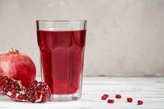 Vidro do suco da romã com fruto fresco da romã Fotografia de Stock