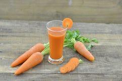 Vidro do suco de cenoura com as cenouras frescas em de madeira Foto de Stock Royalty Free