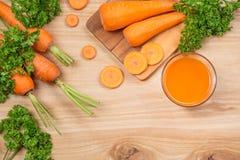 Vidro do suco de cenoura fresco com os vegetais na tabela de madeira Imagem de Stock