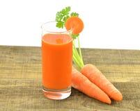 Vidro do suco de cenouras e de cenouras frescas em de madeira Imagens de Stock Royalty Free
