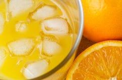 Vidro do suco de fruto com cubos e laranjas de gelo Foto de Stock Royalty Free