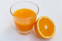 Vidro do suco de laranja com o parcialmente alaranjado no fundo branco Imagens de Stock