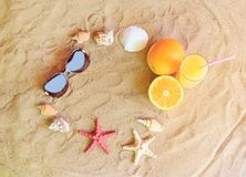 Vidro do suco de laranja, das laranjas, dos óculos de sol, das estrelas do mar e das conchas do mar Imagens de Stock