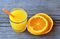 Vidro do suco de laranja fresco e fatias de fruto alaranjado na tabela de madeira rústica Suco de laranja recentemente espremido  Imagens de Stock Royalty Free