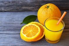 Vidro do suco de laranja fresco, do fruto alaranjado maduro e das fatias na tabela de madeira rústica Suco de laranja recentement Fotografia de Stock Royalty Free