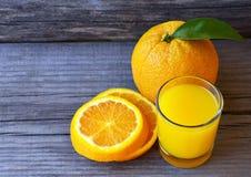 Vidro do suco de laranja fresco, do fruto alaranjado maduro e das fatias na tabela de madeira rústica Suco de laranja recentement Imagens de Stock