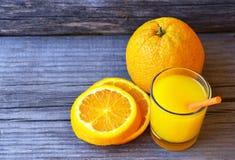 Vidro do suco de laranja fresco, do fruto alaranjado maduro e das fatias na tabela de madeira rústica Suco de laranja recentement Imagens de Stock Royalty Free