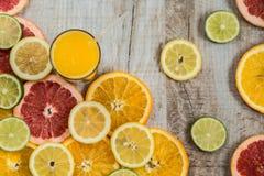 Vidro do suco de laranja no fundo de madeira com fatias de citrino Imagem de Stock Royalty Free
