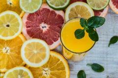 Vidro do suco de laranja no fundo de madeira com fatias de citrino Fotos de Stock