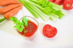 Vidro do suco de tomate com selery, pimenta, cenoura e tomates Imagens de Stock
