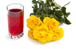 Vidro do suco e de rosas amarelas em um fundo branco Imagem de Stock