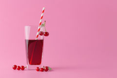 Vidro do suco fresco com as cerejas no fundo brilhante Imagens de Stock Royalty Free