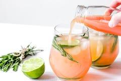 Vidro do suco fresco com cal e alecrins no backg branco da tabela Imagem de Stock