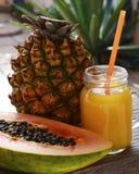 Vidro do suco recentemente espremido com palha bebendo e frutos tropicais maduros do abacaxi e da papaia na tabela de madeira no  Fotos de Stock