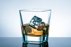 Vidro do uísque com os cubos de gelo na tabela da barra com reflexão na luz - fundo azul do matiz Fotos de Stock