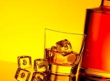Vidro do uísque com os cubos de gelo perto da garrafa na tabela com reflexão, atmosfera amarela morna do matiz Fotografia de Stock Royalty Free